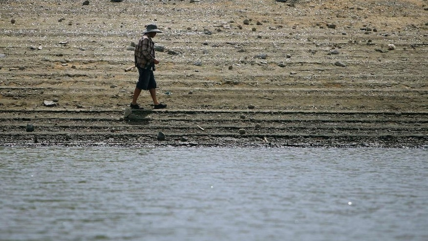 A man walks along the low waterline of La Plata reservoir in Toa Alta, Puerto Rico, Wednesday, May 13, 2015. Puerto Rico imposed strict water-rationing measures Wednesday and Gov. Alejandro Garcia Padilla recently declared a state of emergency given the increasingly dry conditions. (AP Photo/Ricardo Arduengo)