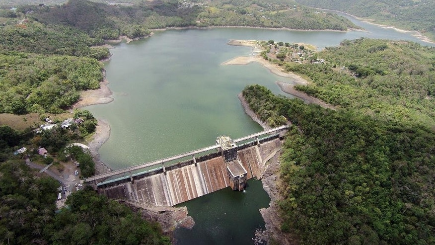 FILE - This July 1, 2014 file aerial photo shows low water level in the La Plata reservoir dam in Toa Alta, Puerto Rico. The island is implementing strict water-rationing measures starting May 13, 2015 amid the dry spell that officials warn could extend into summer. (AP Photo/Ricardo Arduengo, File)