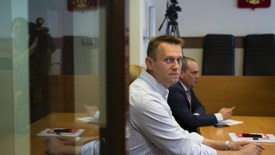Russian opposition activist and blogger Alexei Navalny, front, sits in a courtroom before the hearing in Moscow, Russia, Wednesday, May 13, 2015, to consider the sentence after being convicted in December 2014 of fraud and given a three-and-a-half-year suspended sentence.  The Moscow court has turned down the prosecutors' request to turn the suspended sentence for opposition leader Alexei Navalny into a prison term. (AP Photo/Pavel Golovkin)