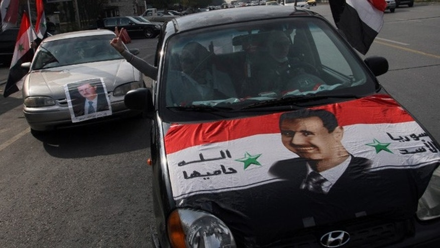 FILE - In this Wednesday, Jan. 22, 2014 file photo, Syrians display national flags and banners with photos of Syrian President Bashar Assad during a pro-government event in Damascus. (AP Photo, File)