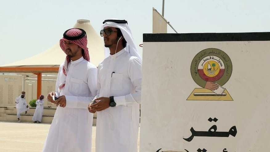 Qatari men wait to vote in the municipal elections at a polling station in Doha, Qatar,Wednesday, May 13, 2015. Voters in Qatar are casting ballots in a rare election in the tiny Gulf nation for members of a municipal council. Wednesday's balloting was the fifth such vote held in the history of Qatar, the oil and natural gas-rich country that will host the 2022 World Cup. (AP Photo/Osama Faisal)