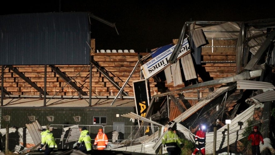 Emergency services personnel clear up damage to Baycorp Stadium after a tornado passed through in Mount Maunganui, New Zealand, Thursday May 14, 2015. Heavy rain caused flooding Thursday that left one man dead, halted train service and blocked highways during the evening commute. Wild weather also hit other parts of the North Island, with a small tornado lifting roofs from homes in the town of Mount Maunganui. (Alan Gibson/New Zealand Herald via AP) NEW ZEALAND OUT, AUSTRALIA OUT