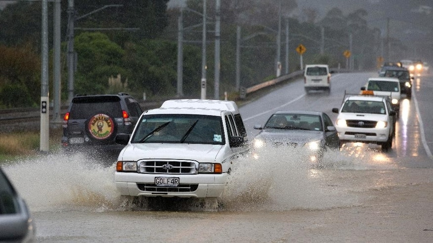 Traffic negotiates a flooded highway north of Wellington on State Highway One, New Zealand, Thursday, May 14, 2015. Heavy rain caused flooding that left one man dead, halted train service and blocked highways during the evening commute. Crews struggled to clear highways, and the shutdown of Wellington's train services delayed travel for many. (Mark Mitchell/New Zealand Herald via AP) NEW ZEALAND OUT, AUSTRALIA OUT