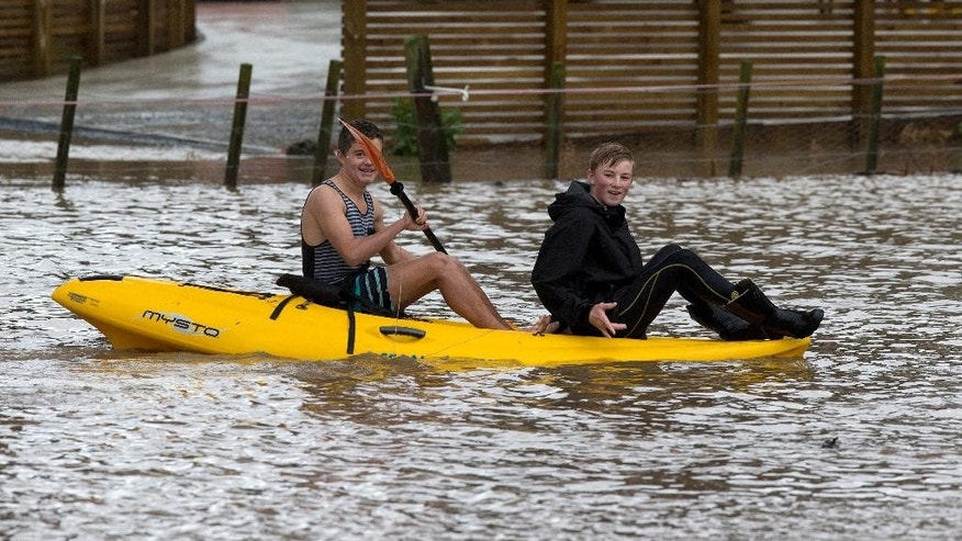 Students Connor Williams, left, and Cooper Wattam use a kayak to cross a flooded paddock in Paraparaumu, north of Wellington, New Zealand, Thursday, May 14, 2015. Heavy rain caused flooding Thursday that left one man dead, halted train service and blocked highways during the evening commute. Crews struggled to clear highways, and the shutdown of Wellington's train services delayed travel for many. (Mark Mitchell/New Zealand Herald via AP) NEW ZEALAND OUT, AUSTRALIA OUT
