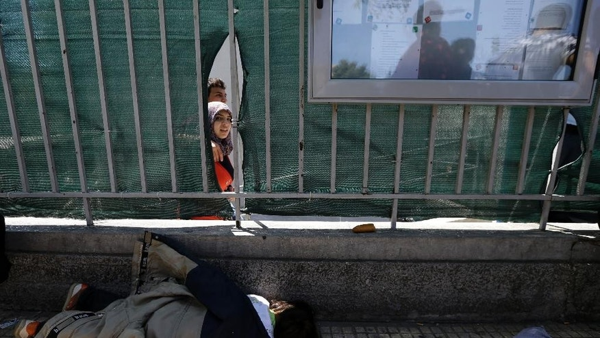 A Syrian child sleeps outside the Central Asylum Center as other leave the building during a protest over a lack of translator facilities and the slow asylum process in Athens, Thursday, May 14, 2015. This year has seen a significant increase in the numbers of refugees from war-torn Middle Eastern and African countries, as well as economic migrants, crossing illegally to Greece. (AP Photo/Thanassis Stavrakis)