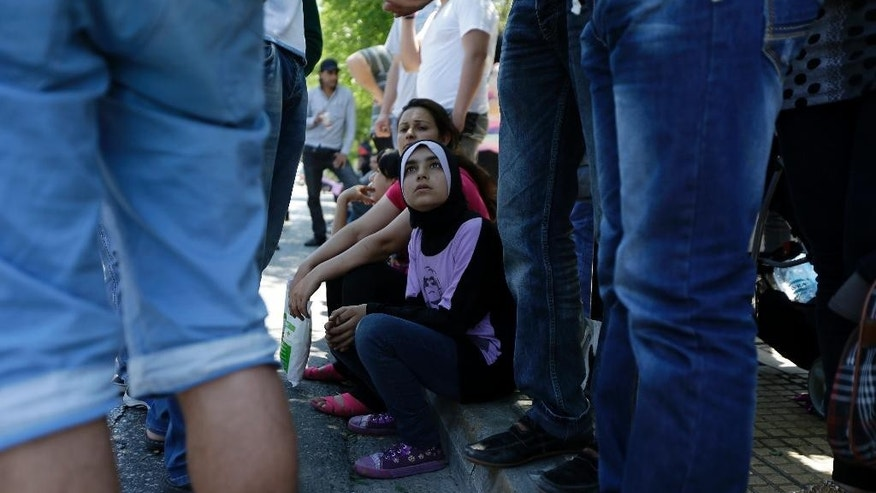 A girl looks at Syrians refugees during a protest over a lack of translator and the slow asylum process outside the Central Asylum Center in Athens, Thursday, May 14, 2015. This year has seen a significant increase in the numbers of refugees from war-torn Middle Eastern and African countries, as well as economic migrants, crossing illegally to Greece. (AP Photo/Thanassis Stavrakis)