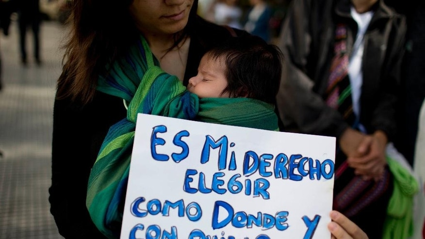"A woman holds her baby and a sign that read in Spanish: ""It's my right to choose how, where, and with whom to give birth"" as she protests restrictions on home births in Buenos Aires, Argentina, Thursday, May 14, 2015. The Argentine Midwives Association is pushing against the Health Ministry's proposal to put restrictions and regulations on home births, saying the number of home births has tripled over last three years as ""people try to avoid the epidemic of caesarian sections."" (AP Photo/Natacha Pisarenko)"