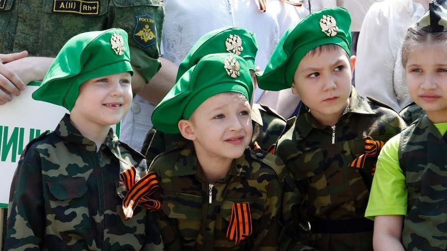 Children wearing specially made uniforms, watch the so-called Kid Parade in Rostov-on-Don, Russia, Thursday, May 14, 2015. Hundreds of children walked past medal-bedecked veterans in a parade marking the 70th anniversary of World War II victory. Thursday's performance in the city of Rostov-on-Don, about 100 kilometers (60 miles) east of the border with Ukraine was held in the city for the sixth straight year, involved about 500 children from pre-school age to the age of 11. (AP Photo)