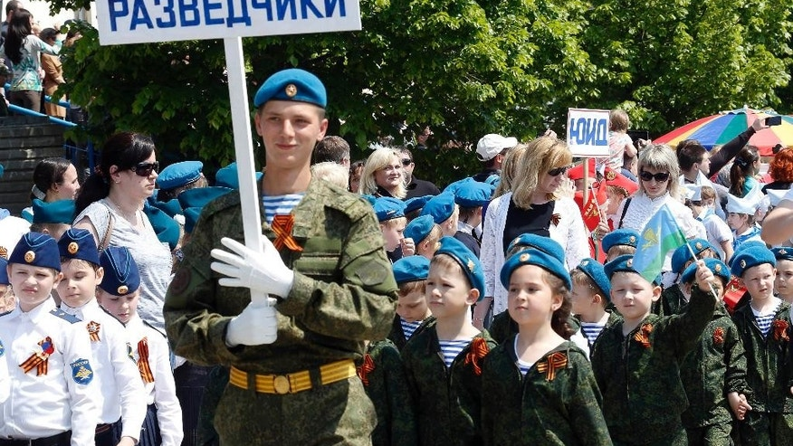 A man in a military uniform with a sign reading Scouts marches with children wearing specially made uniforms during the so-called Kid Parade in Rostov-on-Don, Russia, Thursday, May 14, 2015. Hundreds of children walked past medal-bedecked veterans in a parade marking the 70th anniversary of World War II victory. Thursday's performance in the city of Rostov-on-Don, about 100 kilometers (60 miles) east of the border with Ukraine was held in the city for the sixth straight year, involved about 500 children from pre-school age to the age of 11. (AP Photo)