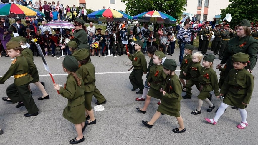 Children wearing specially made uniforms, march in front of WWII veterans,  along a street during the so-called Kid Parade in Rostov-on-Don, Russia, Thursday, May 14, 2015. Hundreds of children walked past medal-bedecked veterans in a parade marking the 70th anniversary of World War II victory. Thursday's performance in the city of Rostov-on-Don, about 100 kilometers (60 miles) east of the border with Ukraine was held in the city for the sixth straight year, involved about 500 children from pre-school age to the age of 11. (AP Photo)