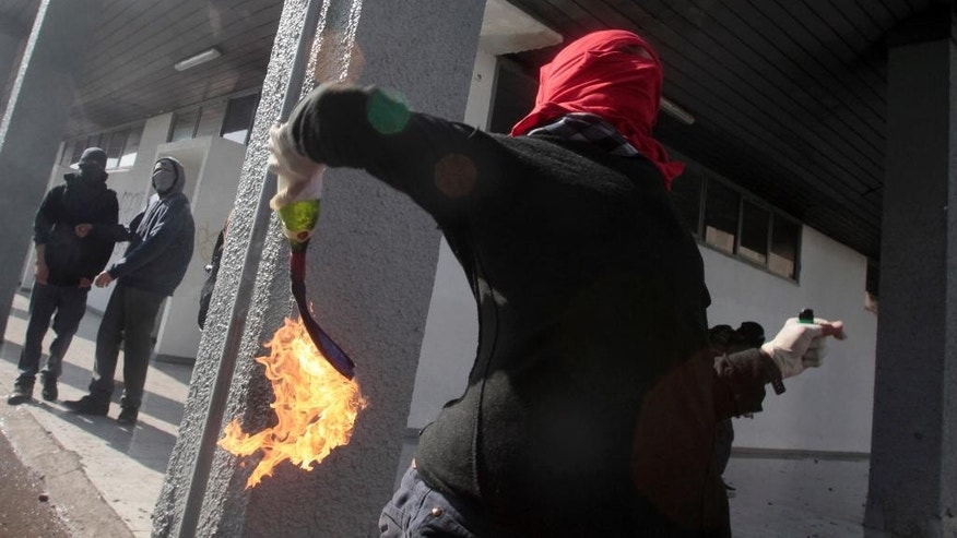 A masked demonstrator readies to throw a petrol bomb towards the police during a protest at the University of Santiago, in Santiago, Chile, Thursday, May 14, 2015. In the capital and other cities across the country, high school and university students marched, for the second time this year, to demand education reform. (AP Photo/Luis Hidalgo)