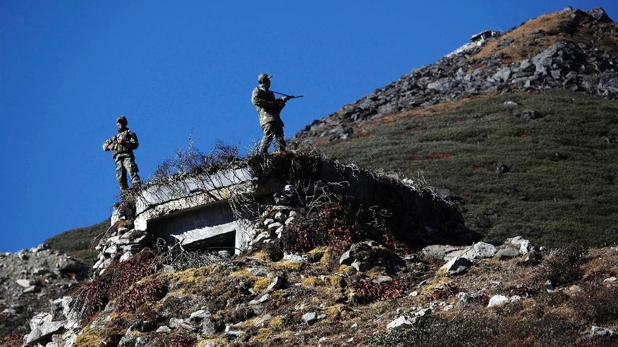 FILE- In this Oct. 21, 2012 file photo, Indian army soldiers keep watch at the Indo China border in Bumla at an altitude of 15,700 feet (4,700 meters) above sea level in Arunachal Pradesh, India. India and China have disagreed for decades over which country controls two chunks of Himalayan territory. China says the northeastern Indian state of Arunachal Pradesh is part of China, while India insists China is illegally occupying Aksai Chin, a rocky and largely empty region far to the northwest. (AP Photo/Anupam Nath, file)