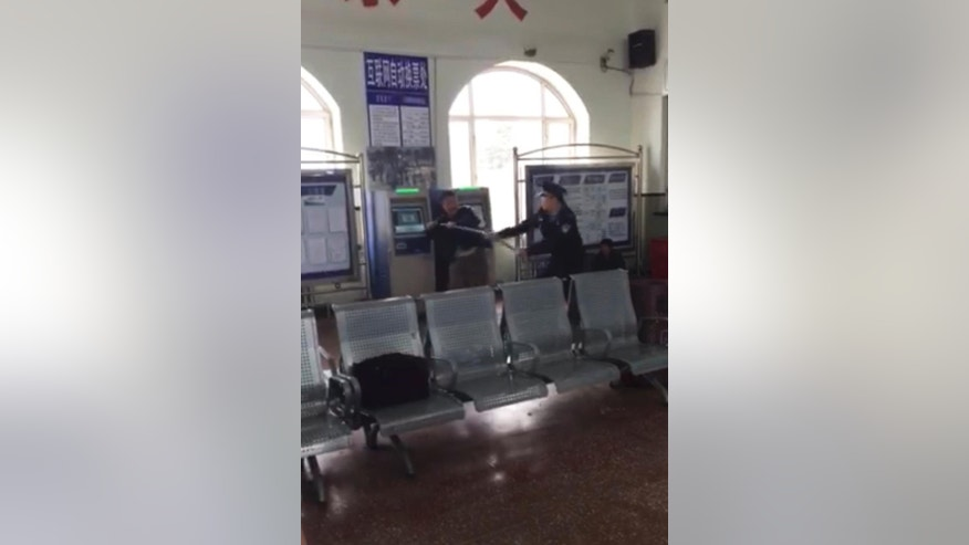 In this still image taken from cellphone video recorded May 2, 2015 by a bystander, Xu Chunhe, left, struggles with policeman Li Lebin, right, in a train station in Qing'an city in northeastern China's Heilongjiang Province. Xu, who was unarmed, was later fatally shot by Li, and China's main state broadcaster released security camera footage of the incident Thursday, May 14, 2015, amid a public outcry over concerns that the policeman used excessive force. (Photo via AP)