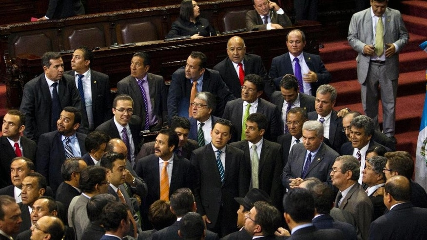 Lawmakers talk during the election of a new Vice President to replace Roxana Baldetti, who resigned on Friday, inside Congress in Guatemala City, Tuesday, May 12, 2015. The discussion was suspended untill Wednesday. The Former Vice President Baldetti resigned Friday, May 8, and gave up her immunity from possible prosecution after her former private secretary, Juan Carlos Monzon Rojas, was accused of being the ringleader of a scheme to defraud the state of millions of dollars by taking bribes in exchange for lower customs duties. (AP Photo/Moises Castillo)