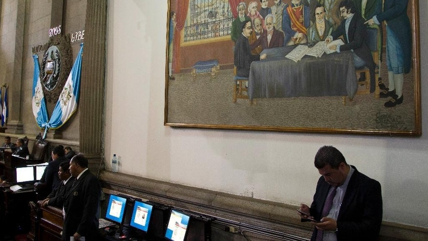 A Congress worker checks his phones during the second election day for a new Gautemalan Vice President inside Congress in Guatemala City, Wednesday, May 13, 2015. The Former Vice President Roxana Baldetti resigned Friday, May 8, and gave up her immunity from possible prosecution after her former private secretary Juan Carlos Monzon Rojas was accused of being the ringleader of a scheme to defraud the state of millions of dollars by taking bribes in exchange for lower customs duties. (AP Photo/Moises Castillo)