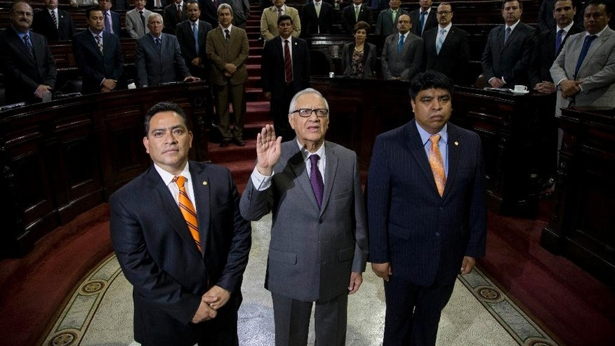 Alejandro Maldonado Aguirre holds up his hand as he is sworn-in as Guatemala's Vice President inside Congress in Guatemala City, Thursday, May 14, 2015. Maldonado replaces former Vice President Roxana Baldetti, who resigned after her private secretary was singled out by authorities as the alleged ringleader of the multimillion-dollar corruption scheme. The men at his sides are unidentified lawmakers. (AP Photo/Moises Castillo)