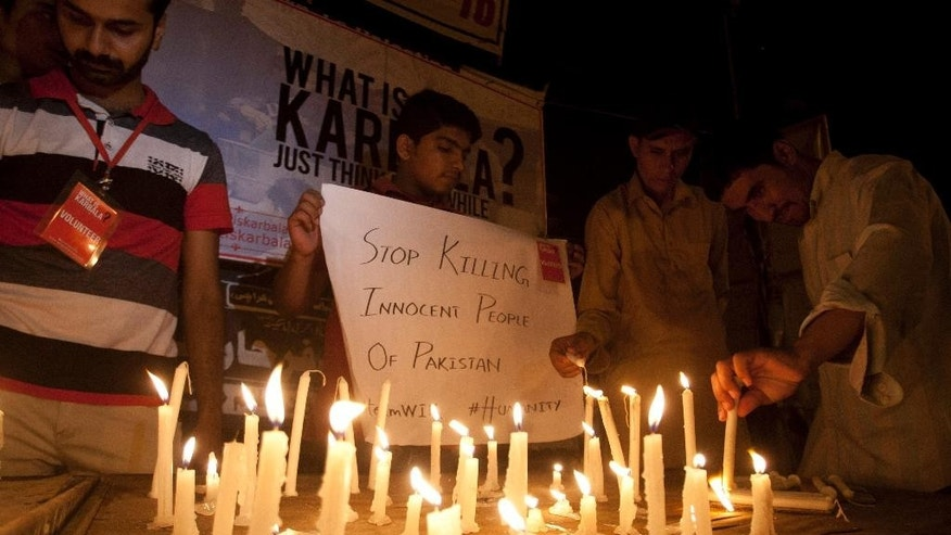 People light candles to protest and show solidarity with the victims of a bus attack in Karachi, Pakistan, Wednesday, May 13, 2015. Gunmen stormed a bus in southern Pakistan and ordered its Shiite Muslim passengers to bow their heads before shooting them, killing dozens of people in the latest attack targeting religious minority, officials said. (AP Photo/Shakil Adil)