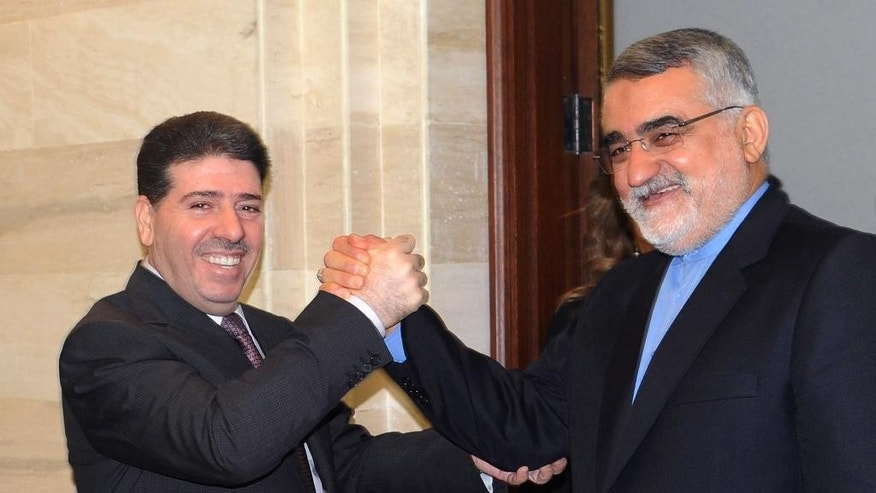 "In this photo released by the Syrian official news agency SANA, Iranian parliament member Alaeddin Boroujerdi, right, shakes hands with Syrian Prime Minister Wael al-Halqi, left, in Damascus, Syria, Thursday, May 14, 2015.  A prominent Iranian lawmaker has criticized the training of some Syrian rebels by the United States and its allies, calling it a ""strategic mistake."" The U.S. program to train Syria's moderate rebels began earlier this month in Jordan and is scheduled to expand to Turkey, Saudi Arabia and Qatar. (SANA via AP)"