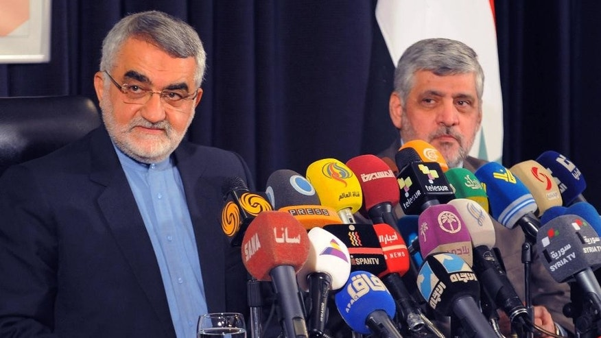 "In this photo released by the Syrian official news agency SANA, Iranian parliament member Alaeddin Boroujerdi, left, speaks during a press conference, in Damascus, Syria, Thursday, May 14, 2015. A prominent Iranian lawmaker has criticized the training of some Syrian rebels by the United States and its allies, calling it a ""strategic mistake."" The U.S. program to train Syria's moderate rebels began earlier this month in Jordan and is scheduled to expand to Turkey, Saudi Arabia and Qatar. (SANA via AP)"