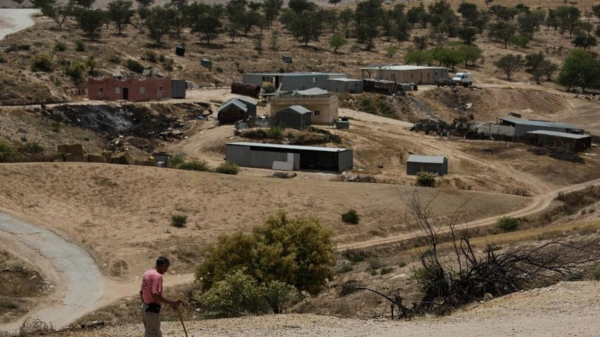 """In this Tuesday, May 12, 2015 photo, a Bedouin man walks through the village of Umm Al-Hiran in the Negev desert, Israel. In a landmark decision, Israel's Supreme Court has cleared the way for the government to uproot the nearly 60-year-old Bedouin Arab village of Umm al-Hiran, a dusty hill of ramshackle dwellings without proper electricity or water hookups, and in its place build """"Hiran,"""" a new Jewish community expected to feature a hotel and country club. (AP Photo/Tsafrir Abayov)"""