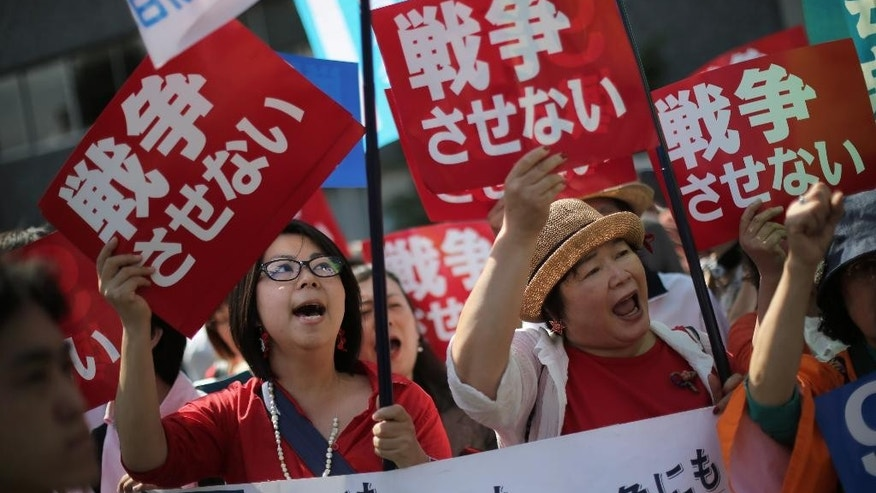 "Hundreds of people stage a rally outside the Japanese Prime Minister's Office in Tokyo, Thursday, May 14, 2015, opposing a set of controversial bills intended to expand Japan's defense role at home and internationally. Banners read ""No War.""  (AP Photo/Eugene Hoshiko)"