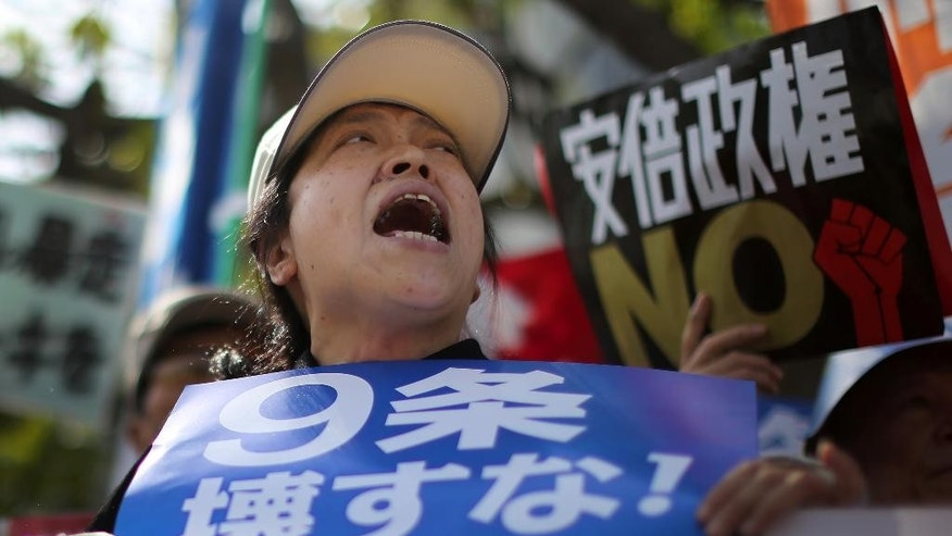 "Hundreds of people stage a rally outside the Japanese Prime Minister's Office in Tokyo, Thursday, May 14, 2015, opposing a set of controversial bills intended to expand Japan's defense role at home and internationally. A banner, front, reads ""Don't destroy Article 9 of the Constitution."" (AP Photo/Eugene Hoshiko)"