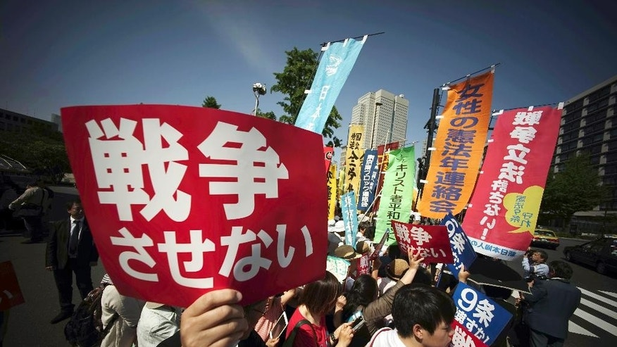 "Hundreds of people stage a rally outside the Japanese Prime Minister's Office in Tokyo, Thursday, May 14, 2015, opposing a set of controversial bills intended to expand Japan's defense role at home and internationally. A banner, left front, reads ""No War.""  (AP Photo/Eugene Hoshiko)"