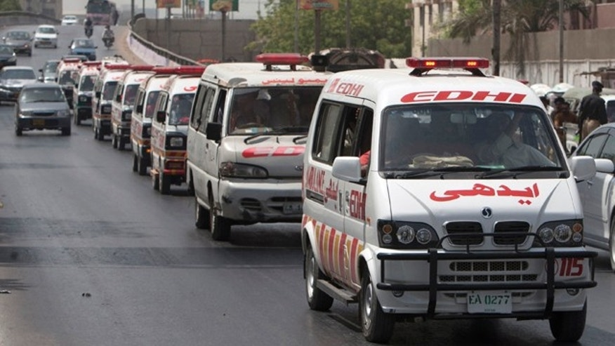 May 14, 2015: Ambulances carry bodies of Wednesday's bus attack victims for burial in Karachi, Pakistan. (AP Photo/Shakil Adil)