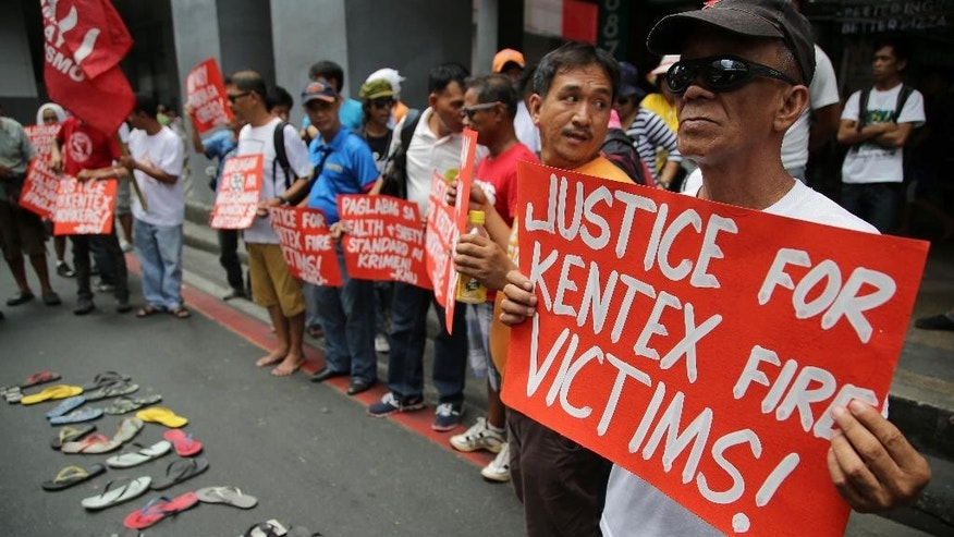 Activists hold slogans while they mourn for victims of a fire that gutted the Kentex rubber slipper factory during a rally in Manila, Philippines on Thursday, May 14, 2015 . The group alleged that the deaths of dozens of trapped workers is due to violations of occupational health and safety standards by owners of the factory. (AP Photo/Aaron Favila)