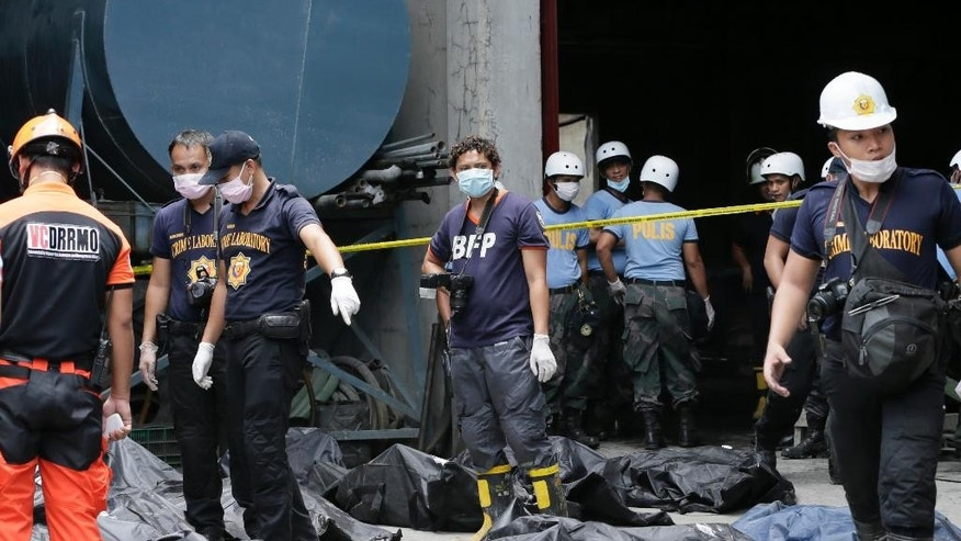 Philippine National Police stand beside the body bags of fire victims at Kentex rubber slipper factory in Valenzuela city, a northern suburb of Manila, Philippines, Thursday, May 14, 2015. On Thursday, police will open a criminal investigation into the incident that killed dozens of people, as a relative of several of the victims said the blaze had trapped workers in the building's second floor where iron grills on windows prevented their escape. (AP Photo/Bullit Marquez)
