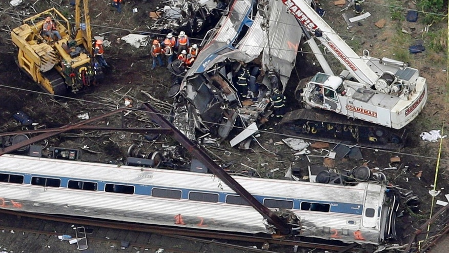 Emergency personnel work at the scene of a deadly train wreck, Wednesday, May 13, 2015, in Philadelphia. More than 200 people aboard the Washington-to-New York train were injured in the derailment that plunged screaming passengers into darkness and chaos Tuesday night. (AP Photo/Patrick Semansky)