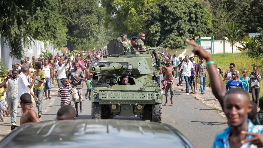May 13, 2015: Burundi army soldiers ride through the streets in an armored vehicle as demonstrators celebrate what they perceive to be an attempted military coup d'etat, in the capital Bujumbura, Burundi.  Police vanished from the streets of Burundi's capital Wednesday as thousands of people celebrated a rumored coup attempt against President Pierre Nkurunziza.