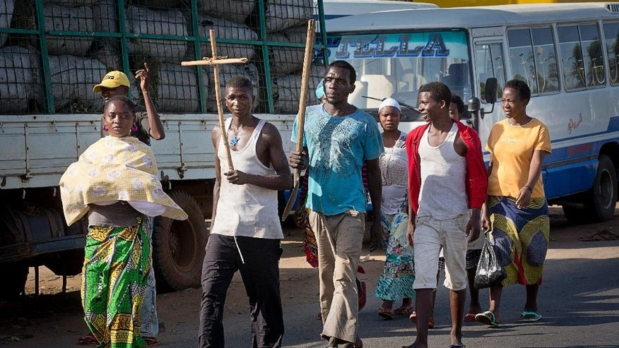 A civilian carries a Christian cross as a sign of impartiality as he and others walk down a major road in the capital Bujumbura, in Burundi Thursday, May 14, 2015. Gunfire and explosions rang out in Burundi's capital on Thursday as military forces backing an attempted coup against President Pierre Nkurunziza battled it out with forces loyal to the elected leader. (AP Photo/Erik Esbjornsson)