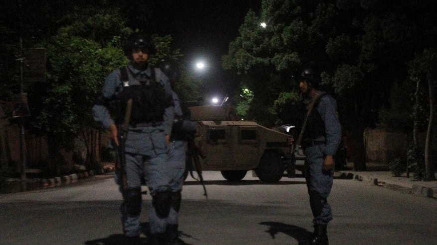 Afghan police officers stand guard near the Park Place Hotel in Kabul, Afghanistan, Thursday, May 13, 2015. Gunmen stormed the guesthouse on Wednesday night as it hosted a party for foreigners. An hourslong siege ended early Thursday morning. (AP Photo/Allauddin Khan)