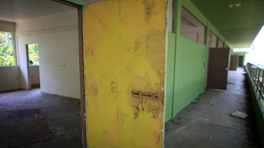 This May 7, 2015 photo shows a hallway in closed Francisco Oller Elementary School in Bayamon, Puerto Rico. The school located just outside the capital is among nearly 100 that have been shuttered as the island struggles through a worsening economic crisis that has prompted many to move to the U.S. mainland over the past decade. (AP Photo/Ricardo Arduengo)