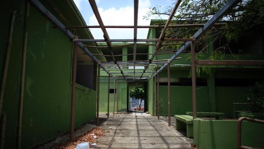 This May 7, 2015 photo shows an empty patio at the closed Francisco Oller Elementary School in Bayamon, Puerto Rico. Driven by a combination of budget cuts and declining enrollment, the loss of so many schools is having a profound impact on communities in the U.S. island territory, forcing many remaining children to commute to new campuses and creating a blight in places already hard-hit by recession. (AP Photo/Ricardo Arduengo)