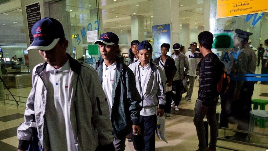 Myanmar fishermen arrive at Yangon International Airport, Thursday, May 14, 2015, in Yangon, Myanmar. Altogether 125 fishermen who returned home to Myanmar were from among the 535 fishermen rescued in the course of an Associated Press investigation into slavery in the seafood industry. All the rescued fishermen will be brought back to Myanmar in separate batches in a chartered flight.  (AP Photo/Khin Maung Win)
