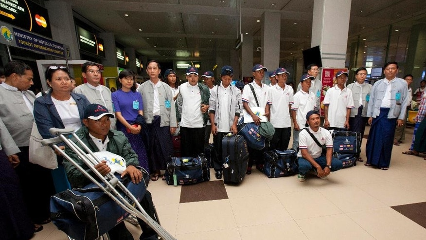 Myanmar fishermen pose for photos with Myanmar officials at Yangon International Airport, Thursday, May 14, 2015, in Yangon, Myanmar. Altogether 125 fishermen who returned home to Myanmar were from among the 535 fishermen rescued in the course of an Associated Press investigation into slavery in the seafood industry. All the rescued fishermen will be brought back to Myanmar in separate batches in a chartered flight.  (AP Photo/Khin Maung Win)