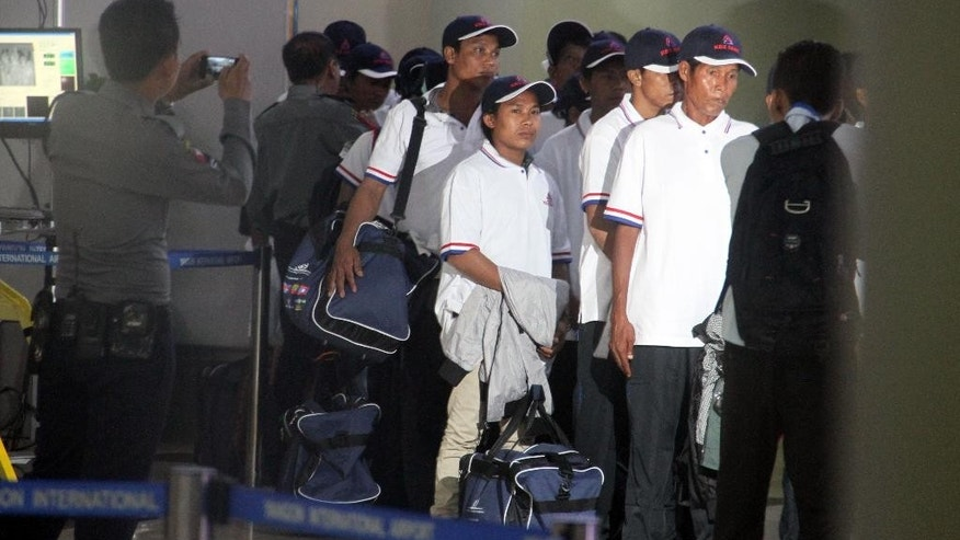 Myanmar fishermen line up to pass immigration at Yangon International Airport, Thursday, May 14, 2015, in Yangon, Myanmar. Altogether 125 fishermen who returned home to Myanmar were from among the 535 fishermen rescued in the course of an Associated Press investigation into slavery in the seafood industry. All the rescued fishermen will be brought back to Myanmar in separate batches in a chartered flight.  (AP Photo/Khin Maung Win)