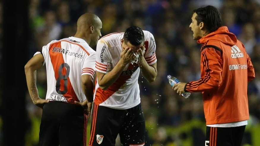 Ramiro Funes Mori of Argentina's River Plate, center, and teammates wash their faces after a caustic substance was thrown at them from the stands, at the start of the second half of a Copa Libertadores round of sixteen soccer match against Boca Juniors in Buenos Aires, Argentina, Thursday, May 14, 2015.  Conmebol delegate Roger Bello of Bolivia and referee Dario Herrera canceled the game after pepper spray was thrown from the stands towards River Plate players before the start of the second half of the game. The La Bombonera stadium has been closed down as a result of the incidents. (AP Photo/Victor R. Caivano)