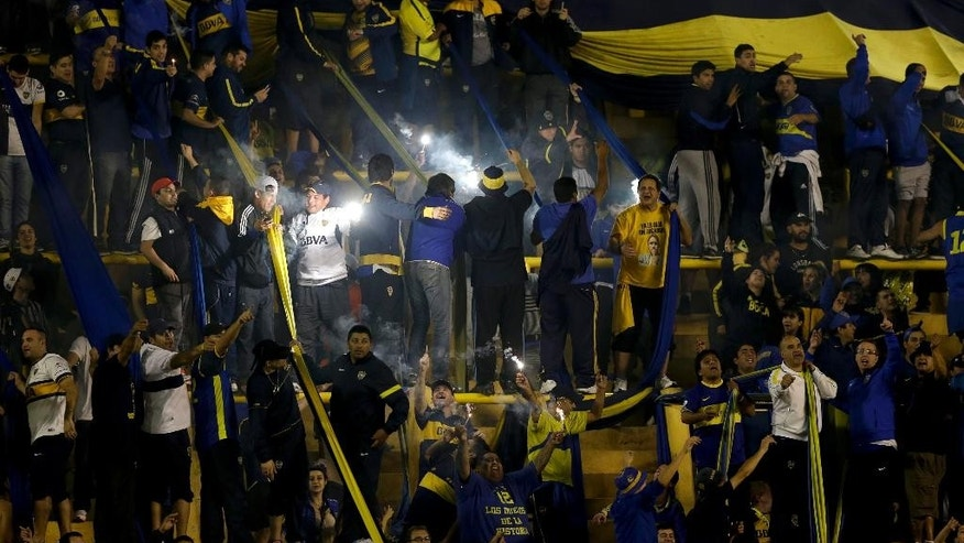 Argentina's Boca Juniors fans shout at River Plate players after the Copa Libertadores soccer match  was canceled in Buenos Aires, Argentina, Friday, May 15, 2015. Conmebol delegate Roger Bello of Bolivia and referee Dario Herrera canceled the game after pepper spray was thrown from the stands towards River Plate players before the start of the second half of the game. The La Bombonera stadium has been closed down as a result of the incidents.(AP Photo/Natacha Pisarenko)