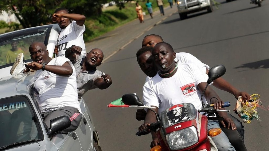 Supporters of President Pierre Nkurunziza celebrate his return in the streets of  Bujumbura, Burundi, Friday, May 15, 2015.  The president's motorcade arrived in Bujumbura after a coup attempt fizzled out, but tensions remained high. (AP Photo/Jerome Delay)