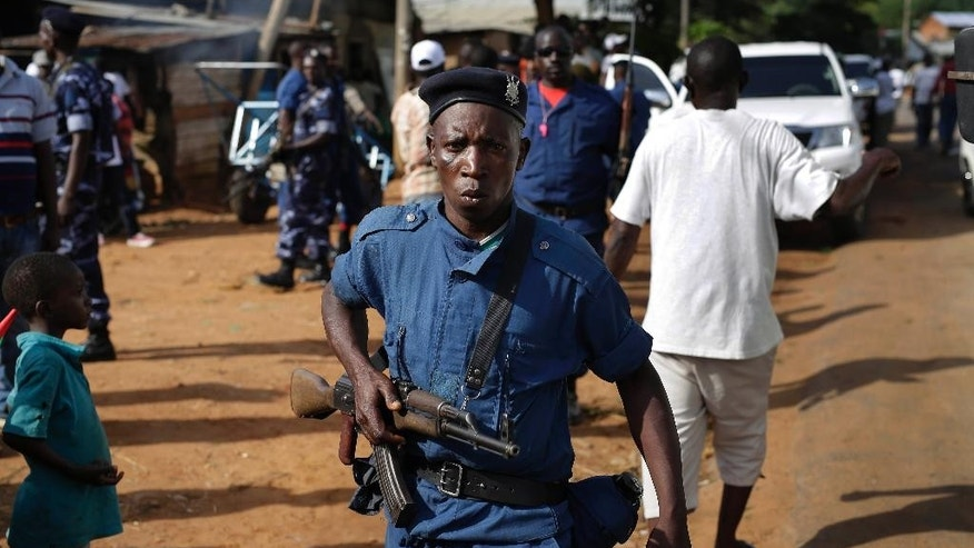Police join supporters of President Pierre Nkurunziza in celebrating his return in the streets of  Bujumbura, Burundi, Friday, May 15, 2015.  The president's motorcade arrived in Bujumbura after a coup attempt fizzled out, but tensions remained high. (AP Photo/Jerome Delay)