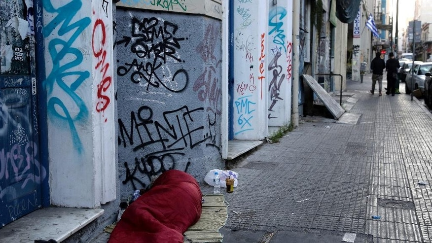 A homeless person sleeps on the street in central Athens, early Wednesday, May 13, 2015. Greece, which is in the midst of protracted bailout talks with creditors, is now officially in recession again according to data released Wednesday, less than a year after it emerged from a six-year depression. (AP Photo/Petros Giannakouris)