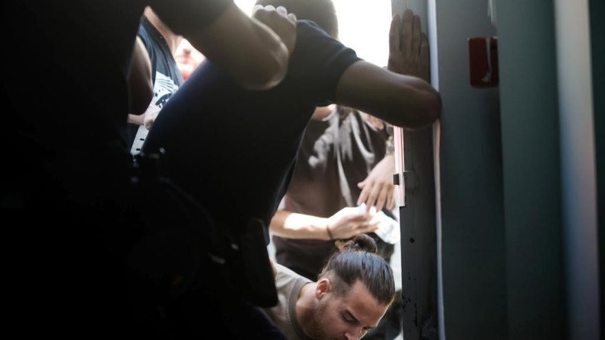 Police scuffle with suspected members of a leftist urban guerrilla group as they try to enter the court of Golden Dawn party in Athens, Friday, May 15, 2015. Lawyers representing the extreme right-wing Golden Dawn party are demanding a change of venue in the trial of party leaders and members for security reasons, following a verbal attack by suspected members of a leftist urban guerrilla group being led to a nearby courtroom for a separate trial. (Nikos Chalkiopoulos/InTime News via AP)  GREECE OUT