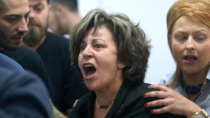 Magda Fyssa, center, mother of Pavlos Fyssas who was stabbed to death, allegedly by a Golden Dawn party volunteer, shouts at members of the extreme right party at the court in Athens, Friday, May 15, 2015. Lawyers representing the extreme right-wing Golden Dawn party are demanding a change of venue in the trial of party leaders and members for security reasons, following a verbal attack by suspected members of a leftist urban guerrilla group being led to a nearby courtroom for a separate trial. (Nikos Chalkiopoulos/InTime News via AP)