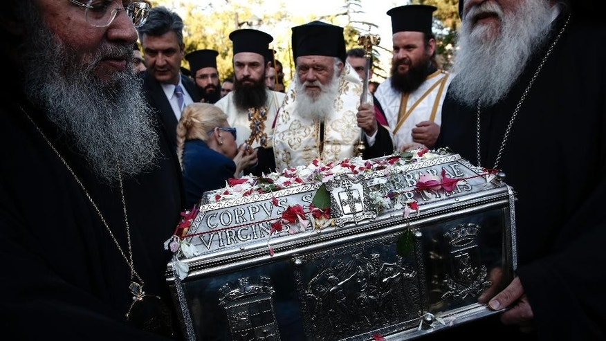 A woman kisses Orthodox Archbishop Ieronymos, center, as he escorts the holy relics of Saint Great Martyr Barbara during a procession to the church of Saint Barbara at Egaleo suburb, west of Athens, on Sunday, May 10, 2015.  The relics, which were kept in Italy, were transferred for the first time in a thousand years to an Orthodox country, with the consent of the Roman Catholic Patriarch of Venice together with the Vatican permission. (AP Photo/Yorgos Karahalis)