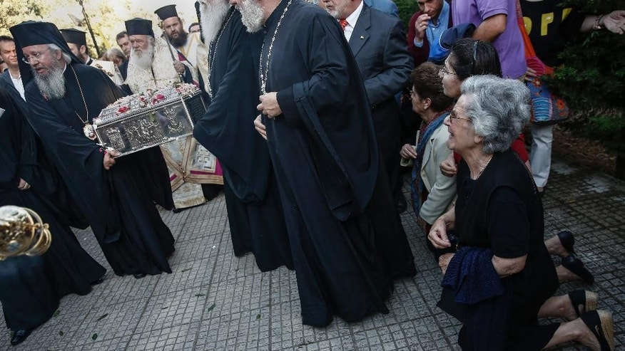 Orthodox faithful kneel as priests carry the holy relics of Saint Great Martyr Barbara during a procession to the church of Saint Barbara at Egaleo suburb, west of Athens, on Sunday, May 10, 2015.  The relics, which were kept in Italy, were transferred for the first time in a thousand years to an Orthodox country, with the consent of the Roman Catholic Patriarch of Venice together with the Vatican permission. (AP Photo/Yorgos Karahalis)