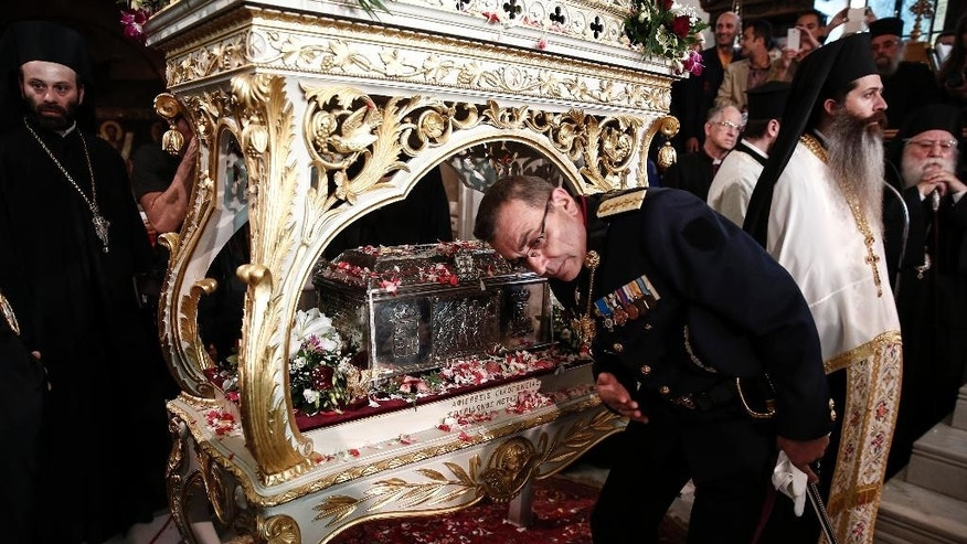 A military officer prays over the holy relics of Saint Great Martyr Barbara inside the church of Saint Barbara at Egaleo suburb, west of Athens, on Sunday, May 10, 2015.  The relics, which were kept in Italy, were transferred for the first time in a thousand years to an Orthodox country, with the consent of the Roman Catholic Patriarch of Venice together with the Vatican permission. (AP Photo/Yorgos Karahalis)