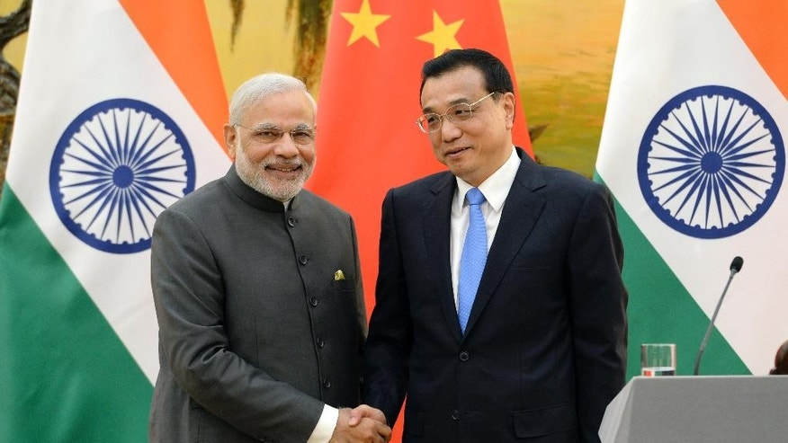 Indian Prime Minister Narendra Modi, left, shakes hands with Chinese Premier Li Keqiang during a press conference at the Great Hall of the People in Beijing, China Friday, May 15, 2015. (Kenzaburo Fukuhara/Pool Photo via AP)